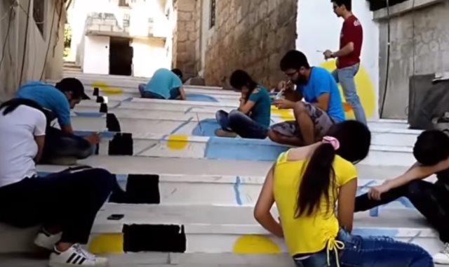 شباب يرسمون لوحات على الحوائط باللاذقية