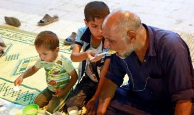 طفل عراقى يطعم أباه