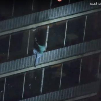 الرجل أثناء نزوله من جدران ناطحة السحاب بطريقة سبايدر مان