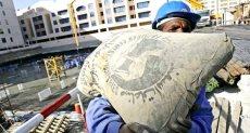 أحد عمال البناء يحمل شيكارة أسمنت