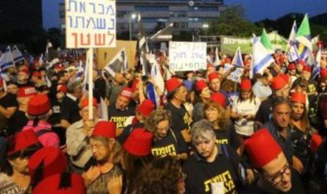 اسرائيليون يتظاهرون بالطرابيش الحمراء