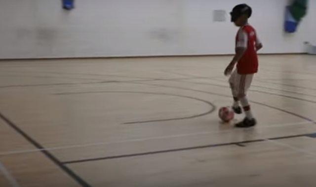 الفتى ميكي يمارس لعب كرة القدم