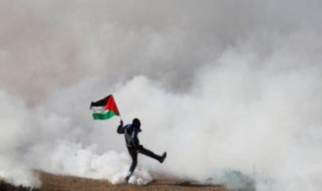 علم فلسطين وسط غاز الاحتلال