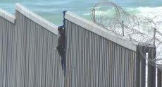 مهاجرون يتسلقون الجدار بين أمريكا والمكسيك