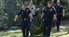 رجال الشرطة يحملون الدب