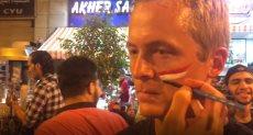 أحد الأجانب يرسم علم مصر على وجهه