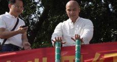مدرب صينى يحاول رفع العبوات المعدنية بدون أصابع