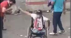 شاب عراقى معاق يساعد المتظاهرين فى التخلص من آثار الغاز المسيل