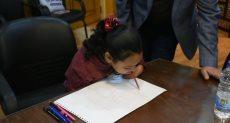 """محافظ أسوان يكافئ طفلة مصابة بضمور لموهبتها فى الرسم بـ""""فمها"""""""