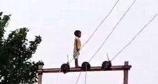 الصبى فوق أعمدة اكلهرباء