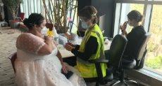 العروس خلال تلقي اللقاح بفستان زفافها